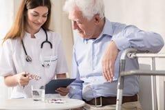 Infermiere gli che dà le medicine pazienti immagini stock libere da diritti