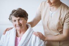 Infermiere grazioso della testarossa in uniforme beige con le sue mani sulle spalle senior della donna immagini stock