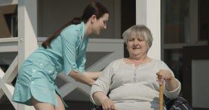 Infermiere Helping da camminare alla donna anziana al pensionato felice di casa di cura che sorride sul colpo di Sunny Day sulla  video d archivio