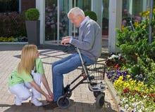 Infermiere Helping Senior Man con il camminatore per legare le scarpe Immagine Stock