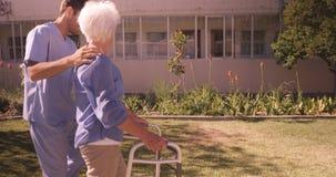 Infermiere maschio che assiste una donna senior per camminare in giardino stock footage