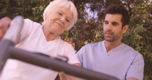 Infermiere maschio che assiste una donna senior per camminare nel cortile archivi video