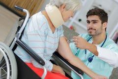 Infermiere maschio che fa iniezione vaccino alla donna anziana fotografia stock libera da diritti