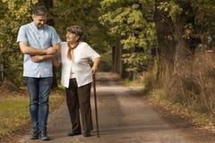 Infermiere maschio che sostiene donna felice con il bastone da passeggio nella foresta fotografia stock