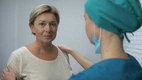 Infermiere preoccupantesi che sostiene donna adulta con la cattiva diagnosi, cancro nelle fasi iniziali archivi video