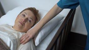 Infermiere preoccupantesi che sostiene paziente anziano disperato che si trova nel letto di ospedale, malattia archivi video