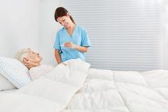 Infermiere su febbre che misura una donna senior fotografia stock