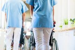 Infermieri che spingono gli anziani in sedia a rotelle attraverso la casa di cura immagini stock libere da diritti