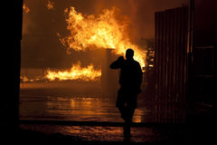 Inferno. Silhouette of firefighters Natural disaster - fire / Burnig house Royalty Free Stock Images