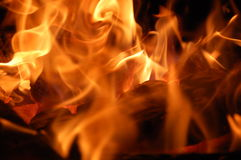 Inferno. A hot fire twirl and swirl as it eats wooden logs Stock Photos