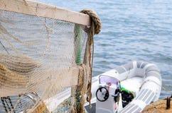 Inferriata coperta nella rete da pesca sul bacino con la barca Fotografie Stock