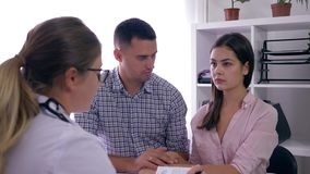 Infertility woman with husband at consultation with doctor found out bad news about health and was upset stock footage