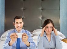 Infidelity in social networks. Woman unhappy with her husband in bed with being unfaithful in social networks royalty free stock photos
