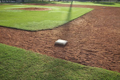 Infield di baseball della gioventù dal lato della prima base alla luce di mattina Fotografie Stock