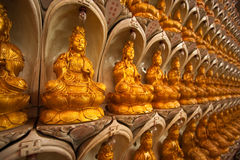Infinite buddha. Repeated Buddha statues lined on a wall. Taken at Kek Lok Si, Penang Malaysia Royalty Free Stock Photo
