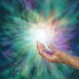 The Infinite Spiral of Life. Open palm with a bright white spiraling light form floating above expanding outwards on a green and purple ethereal energy Stock Images