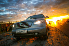 Infiniti FX35. NOVYY URENGOY, RUSSIA - JULY 2. 2017: Grey motor car Infiniti FX35 at the background of the dawn during the midnight sun Stock Image