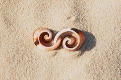 Infinito del símbolo de las cáscaras en la playa, diseño gráfico del elemento fotografía de archivo