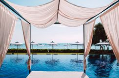 Infinity beach pool with beach bed and white umbrellas - Summer tropical resort royalty free stock photos