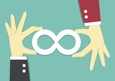 Infinity cooperation. Two businessman's hand carry white infinity symbol on blue background Stock Photo