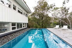 Infinity edge pool in backyard of mid century Australian home. Infinity edge pool in backyard of mid century Australian luxury home royalty free stock photos