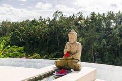 Infinity edge pool with buddha statue Royalty Free Stock Photo