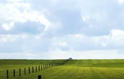 Infinity fence. Fence extending over the horizon in a featureless meadow Royalty Free Stock Photos