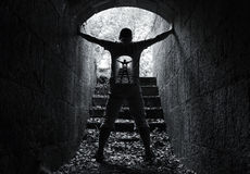 Infinity inner world concept, young man in tunnel. Infinity inner world concept, young man stands in dark stone tunnel with glowing end Stock Image