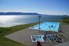 Infinity outdoor pool overlooking fjord mountains in Hofsos in northern Iceland royalty free stock photos