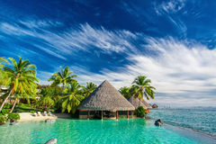 Infinity pool with artificial beach and bar next to tropical ocean royalty free stock photography