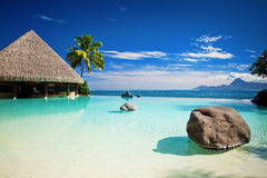 Infinity pool with artificial beach and ocean royalty free stock images