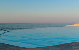 Infinity pool on the beach at sunset Royalty Free Stock Image