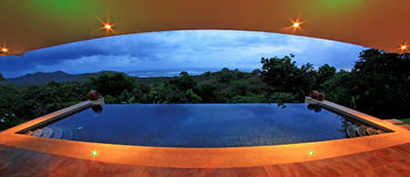 Infinity pool of a luxury house with view of the rainforest and beach, fisheye perspective, Costa Rica Royalty Free Stock Photos