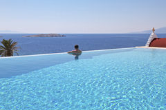 Infinity Pool and Man Mykonos Stock Images