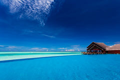 Infinity pool over tropical lagoon with blue sky stock image