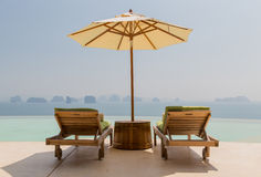 Infinity pool with parasol and sun beds at seaside royalty free stock images