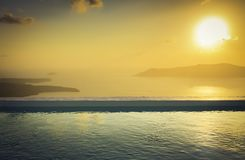 Infinity pool on the rooftop at sunset in Santorini Island Stock Image