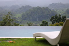 Infinity pool, sun lounger, tropical rainforest view. Bali, Indonesia. Royalty Free Stock Images