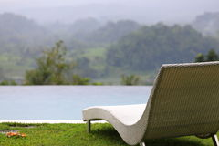 Infinity pool, sun lounger, tropical rainforest view. Bali, Indonesia. Royalty Free Stock Photos