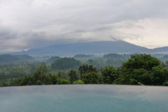 Infinity pool, tropical rainforest, volcano top in clouds. Million dollar view. Vacation house, villa. Bali, Indonesia. Royalty Free Stock Photos