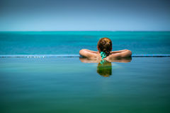 Infinity Pool in Turks and Caicos. A caucasian female model with brown hair is relaxing in an infinity pool and looking out into a bright blue Caribbean Sea from Royalty Free Stock Images