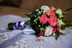 Infinity sign of the rings, wedding rings on a white background,wedding bands. Bouquet of pink and white roses, groom's fees, the preparation for the wedding stock photography