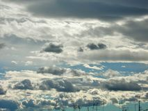 Antennas skyline under white clouds flying. Stratocumulus. Grey and white stratocumulus clouds in the blue sky over the town Royalty Free Stock Image