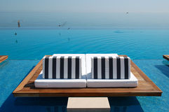 Infinity swimming pool by beach Royalty Free Stock Image