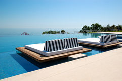 Infinity swimming pool by beach Stock Photography
