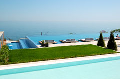 Infinity swimming pool by beach at the modern luxury hotel Stock Photo