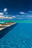 Infinity swimming pool on the beach of tropical island with whit Royalty Free Stock Photo