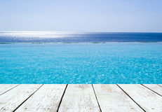 Infinity swimming pool  and empty wooden plank Royalty Free Stock Photography
