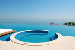 Infinity swimming pool with jacuzzi by beach Stock Images