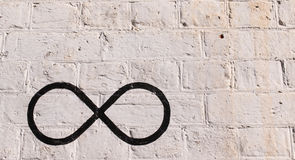 The infinity symbol drawn in black on a brick wall. Painted in white. Normal colored brick wall on the side royalty free stock photo
